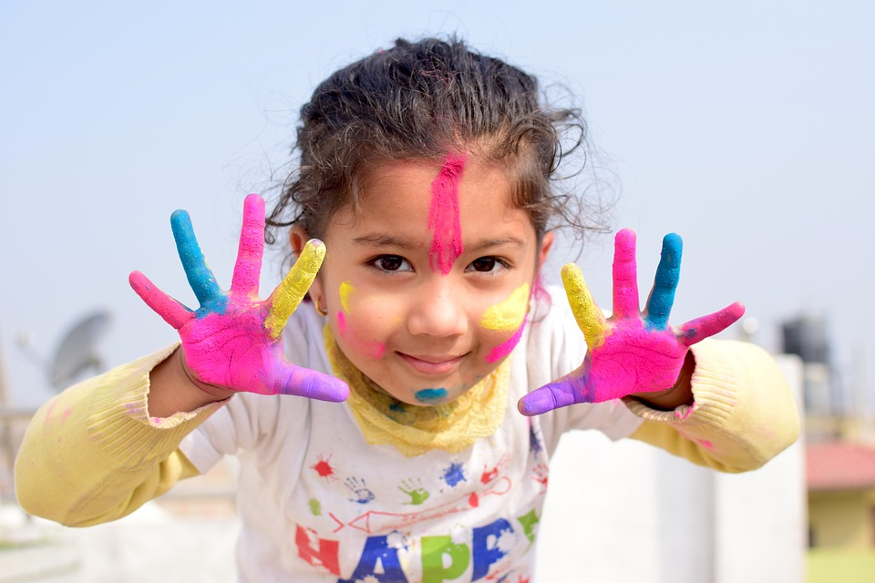 Decorative image of a child with colourful paint on their hands and face